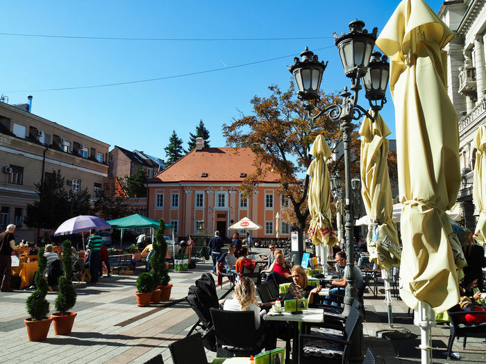 European Cities Novi Sad Serbia Eastern Europe Balkans Europe Outdoors Street Photography Travel Destinations Clear Blue Sky Architecture Public Places Facades Sunlight Built Structure Building Exterior City cityscapes Group Of People Incidental People Day Street Lamp Post Plant Pedestrian Zone