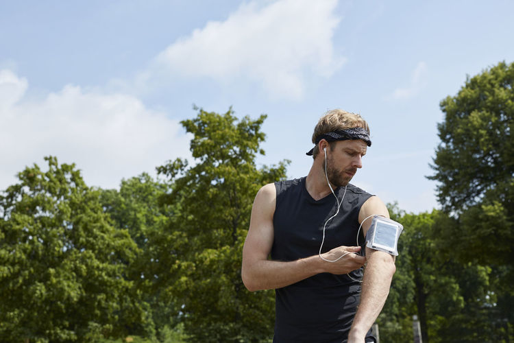 Man listening music while exercising against trees
