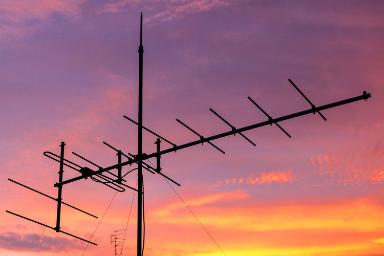 Low angle view of antenna against cloudy orange sky during sunset
