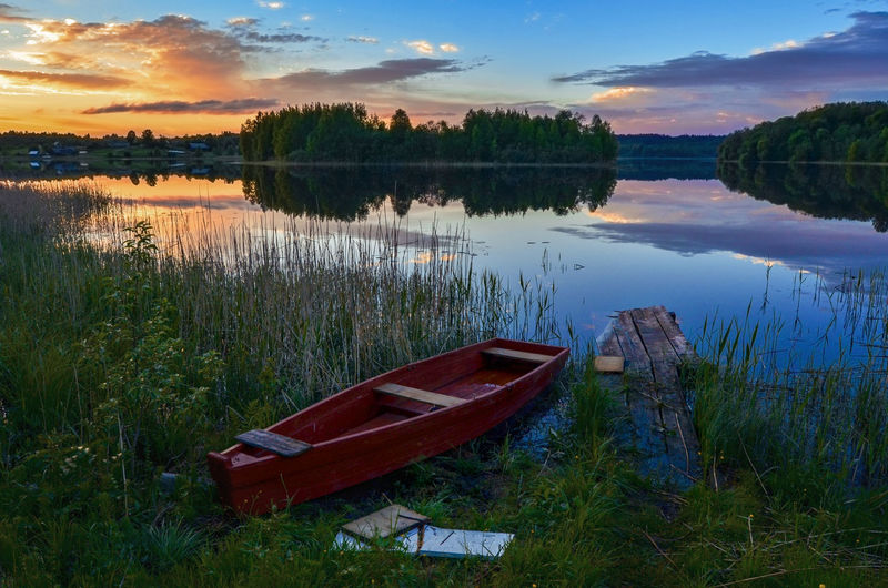 Water Plant Nautical Vessel Sky Reflection Tranquility Cloud - Sky Lake Tranquil Scene Scenics - Nature Grass Nature Beauty In Nature Transportation Mode Of Transportation No People Sunset Tree Moored Outdoors Rowboat