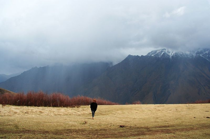 Young woman walking on field by mountains against cloudy sky
