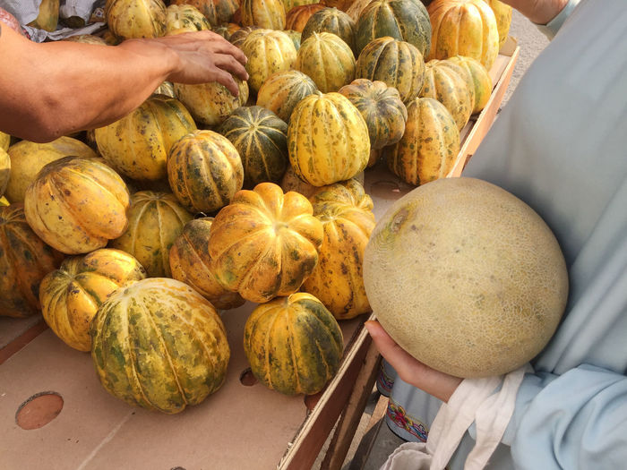 Midsection of customer with squash by customer with cantaloupe