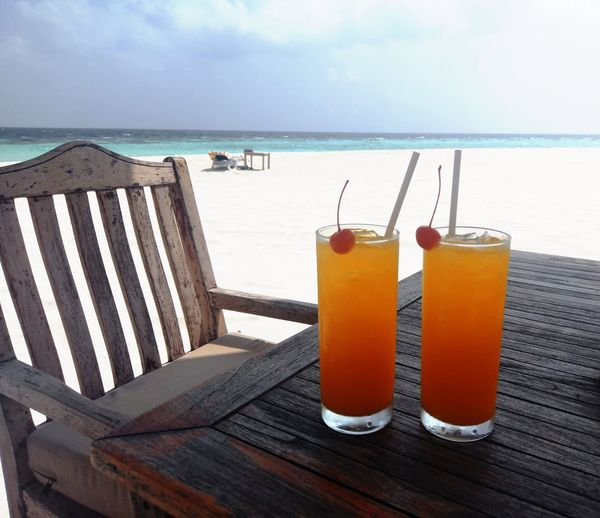 Close-up of drink on table at beach against sky