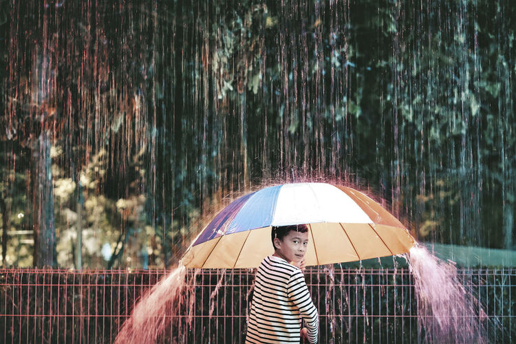 Portrait of boy holding umbrella during rainy season