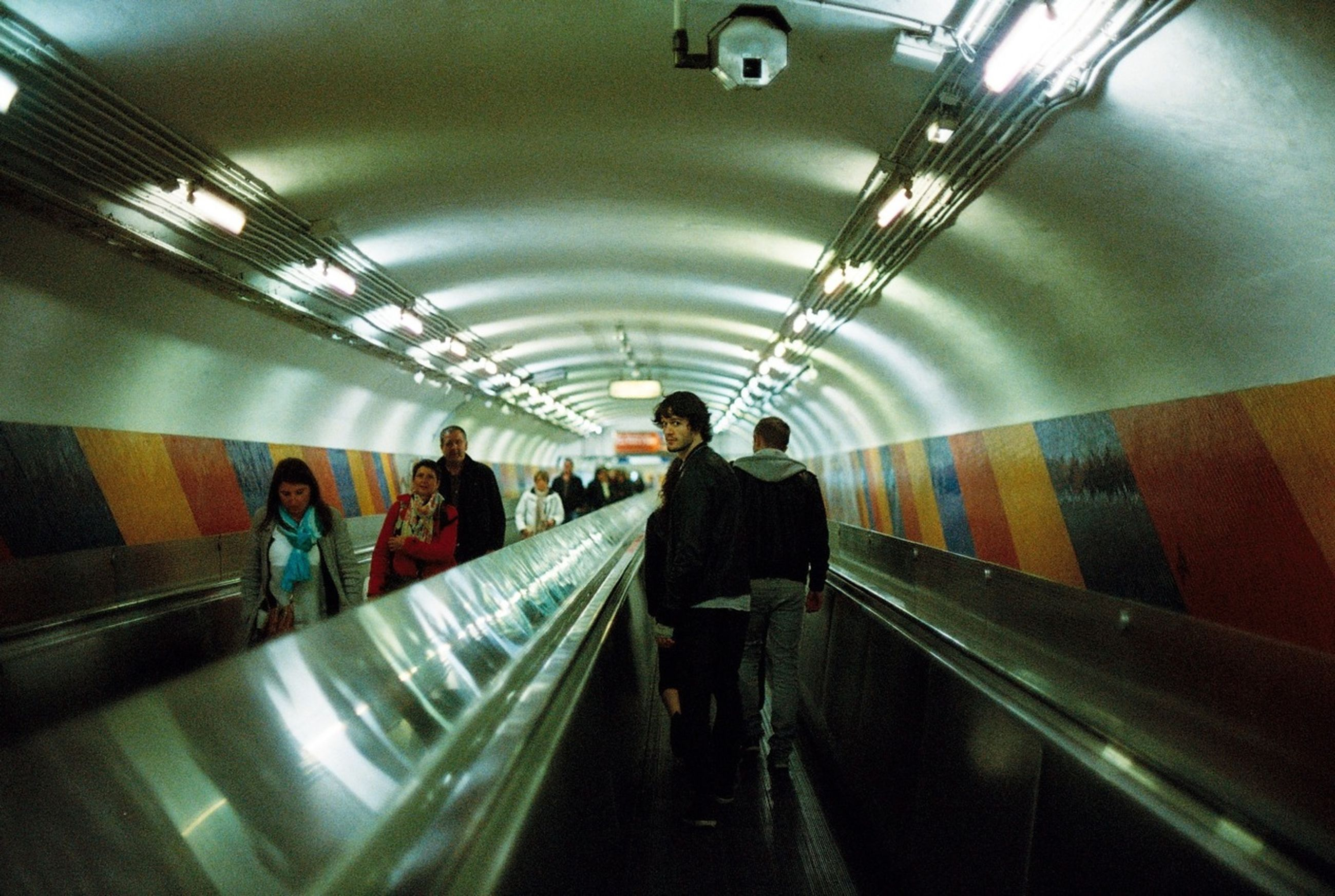 indoors, tunnel, illuminated, lifestyles, ceiling, full length, men, walking, rear view, subway, architecture, built structure, the way forward, leisure activity, escalator, lighting equipment, subway station, person