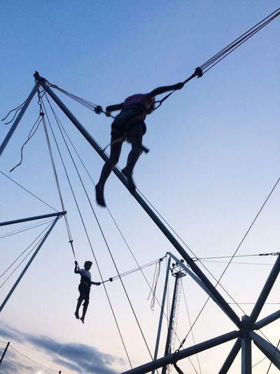 Low angle view of men hanging on rope against sky