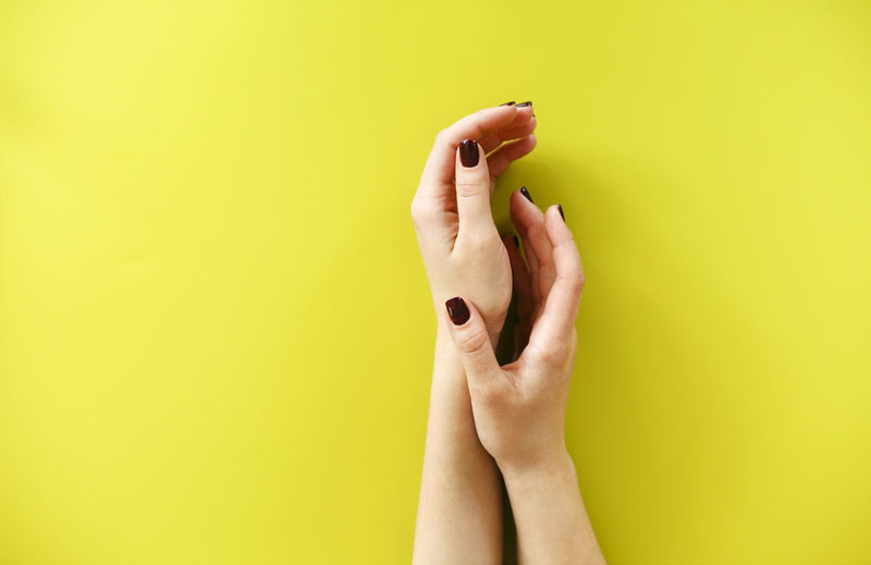 Cropped hands of woman over colored background