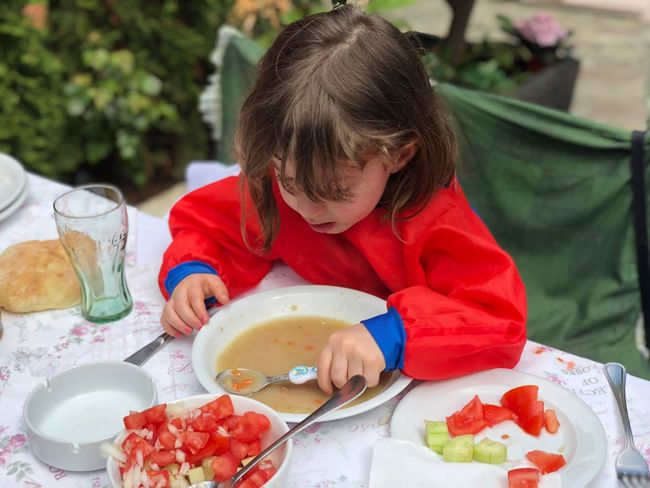 Child Childhood One Person Innocence Kitchen Utensil Real People Front View Table Eating Utensil Plate High Angle View Food And Drink Headshot Holding Looking Down Focus On Foreground Casual Clothing Food Lifestyles Hairstyle
