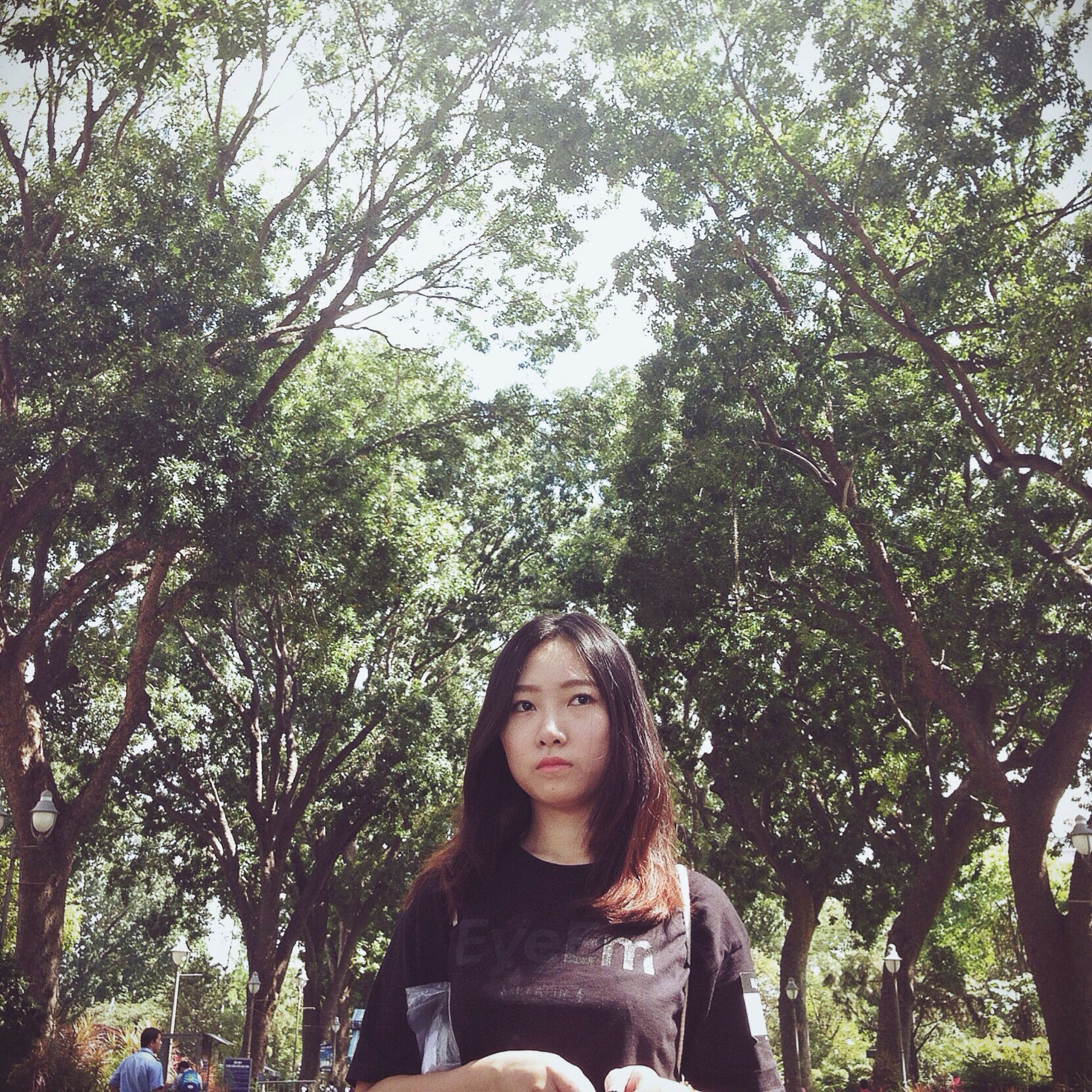tree, lifestyles, young adult, leisure activity, growth, casual clothing, low angle view, looking at camera, young women, nature, front view, park - man made space, portrait, person, day, branch, outdoors, standing
