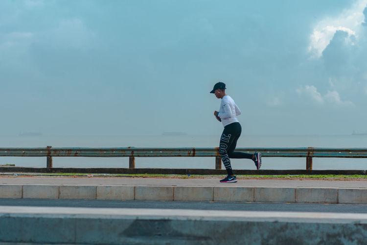 Full length of man standing on bridge against sky