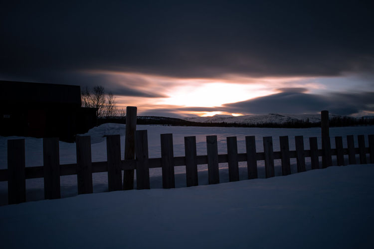 Wooden posts in winter against sky during sunset