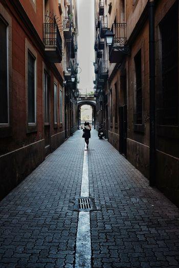 Rear view of man walking on narrow street amidst buildings