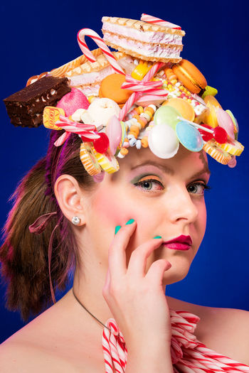 Portrait Of Woman Eating Waffle Against Blue Background