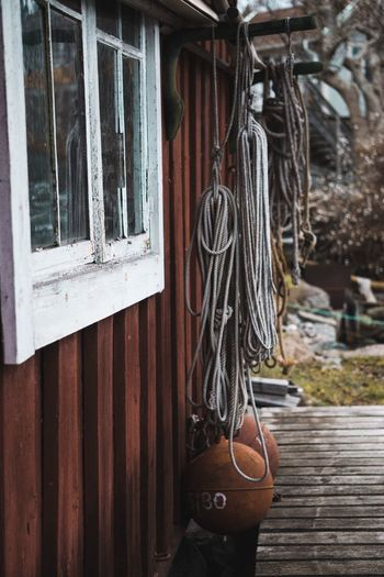 Buoy hanging with rope outside of wooden cabin