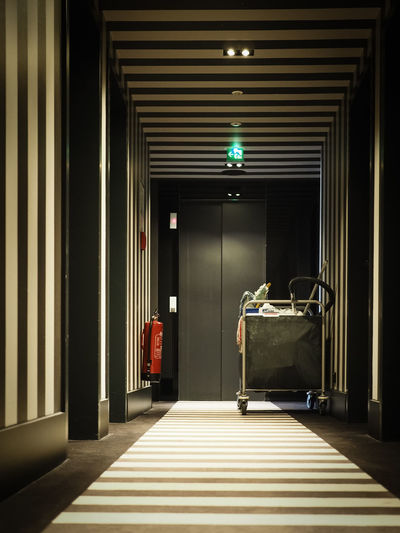Cleaning Cart And Fire Extinguisher In Illuminated Hotel Corridor
