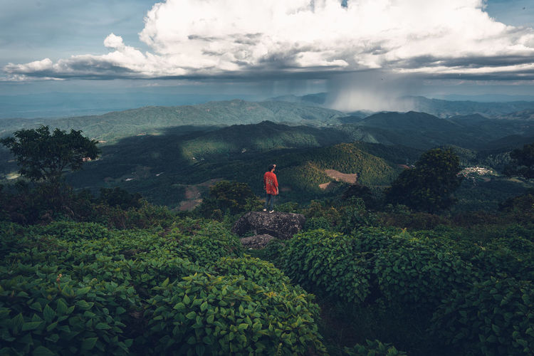 High angle view of man standing on mountains against cloudy sky