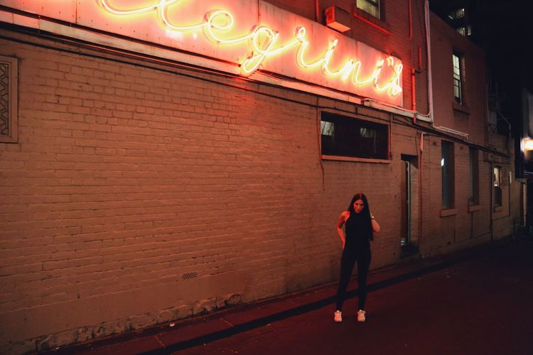 Full length of woman standing in illuminated city at night