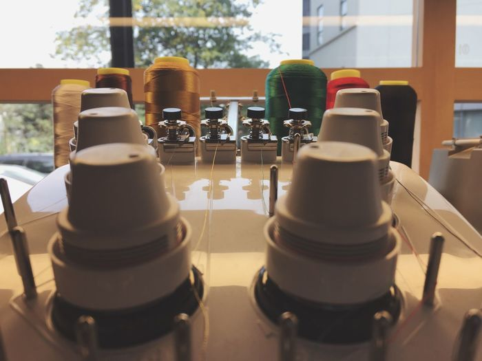 Close-up of sewing machine with thread spools in factory