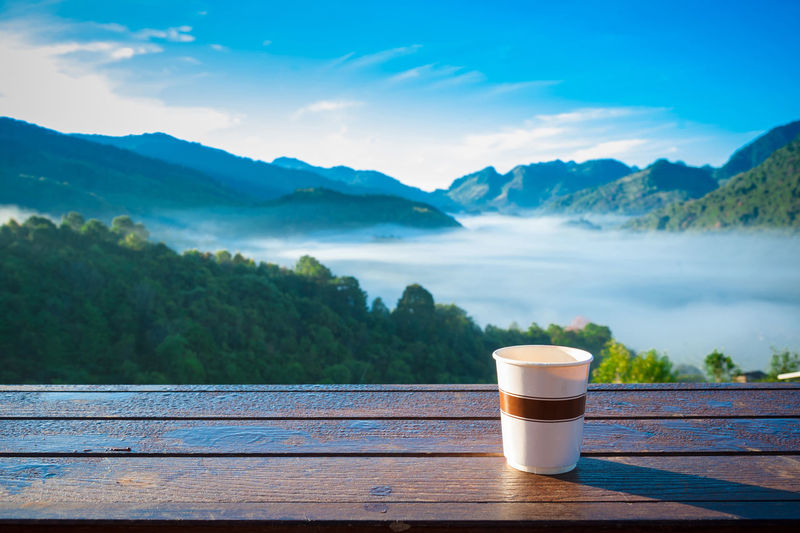 Coffee cup on table by lake against sky