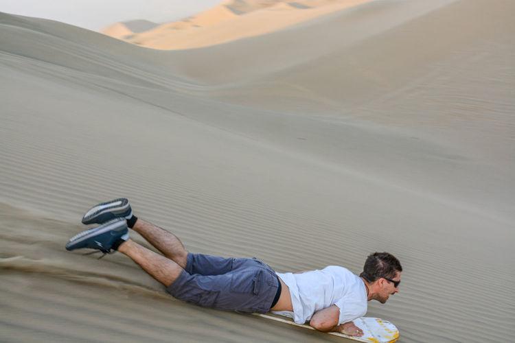 Full length of man sandboarding in desert