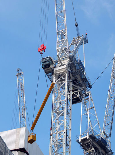 tall construction cranes working on a large development site with concrete large structure Construction Site Crane - Construction Machinery Construction Industry Built Structure Clear Sky Machinery Metal Low Angle View Sky Blue Tall - High Outdoors