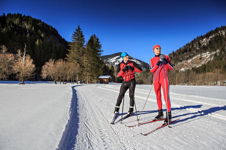 People skiing on snowy field against trees