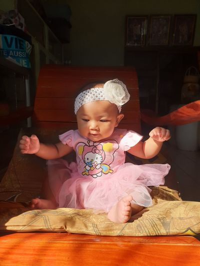 Cute baby girl sitting on floor at home