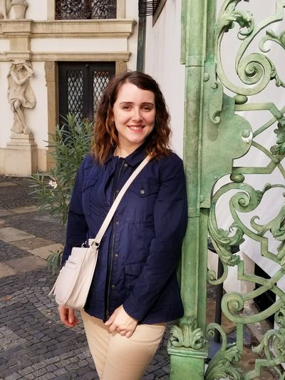 Portrait of smiling young woman standing by gate