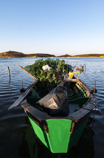 Lobster traps in boat on take against clear sky