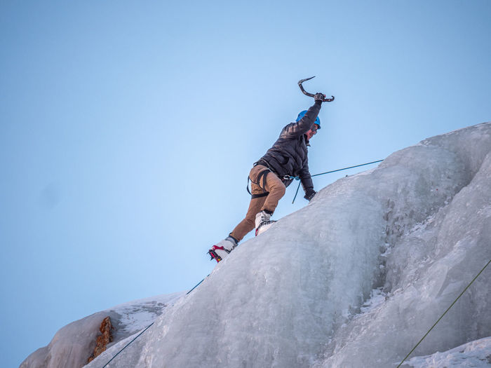 Low angle view of hiker climbing ice