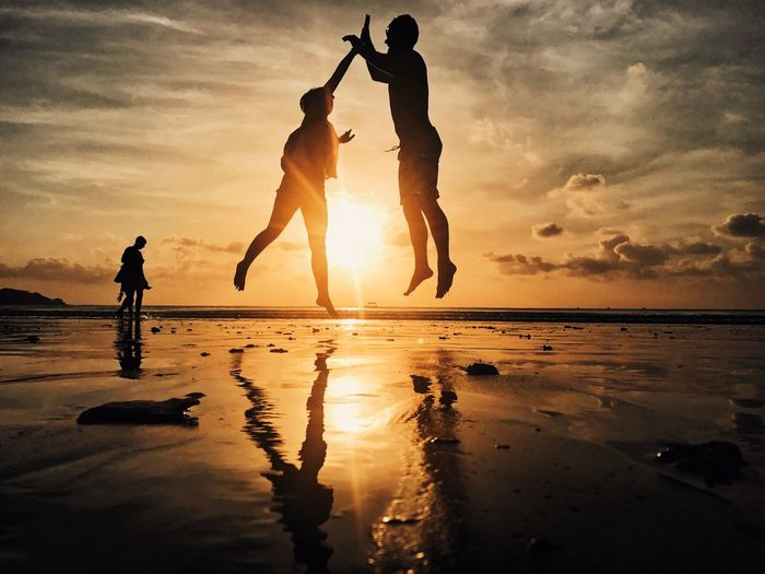 Silhouette friends jumping at beach against sky during sunset
