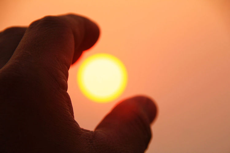 Optical Illusion Of Man Holding Sun During Sunset