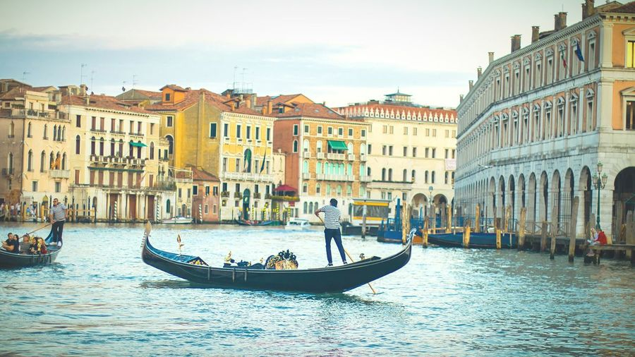 Rear view of man on gondola sailing in canal amidst buildings