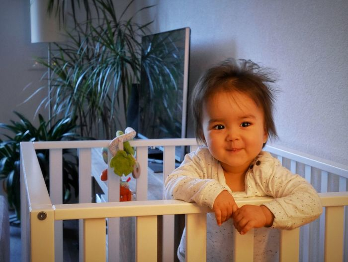Portrait Of Cute Smiling Baby Girl In Crib At Home