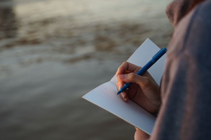 Midsection of man writing in book at sea