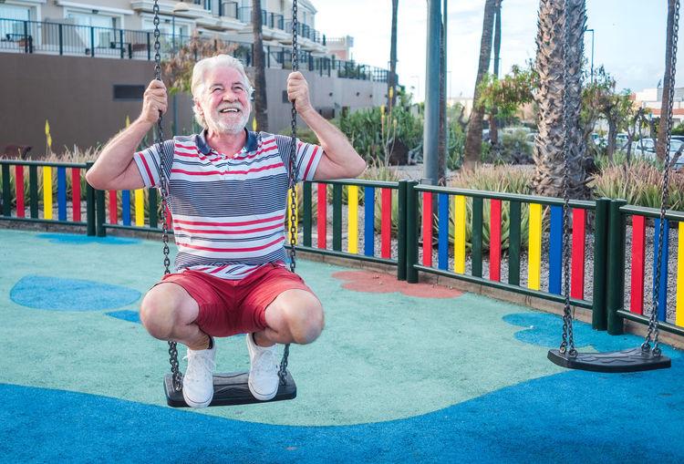 Smiling senior man sitting on swing in park