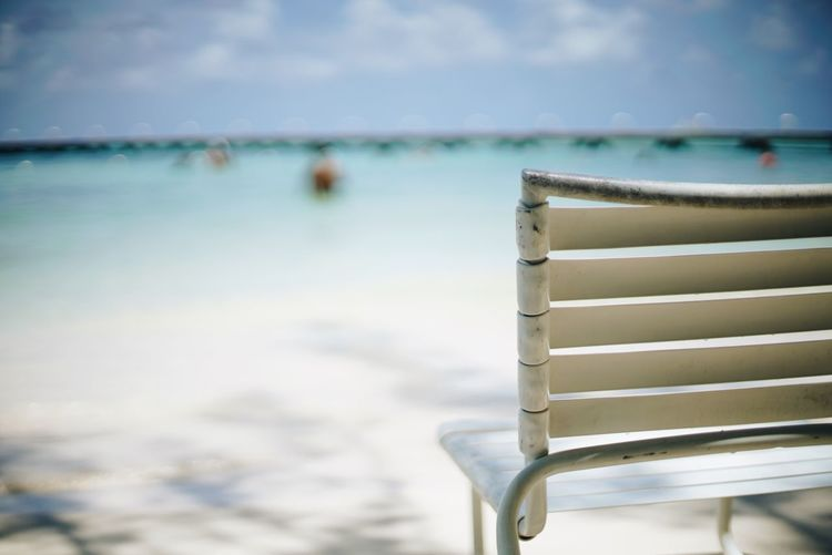 Close-up of empty chair at beach