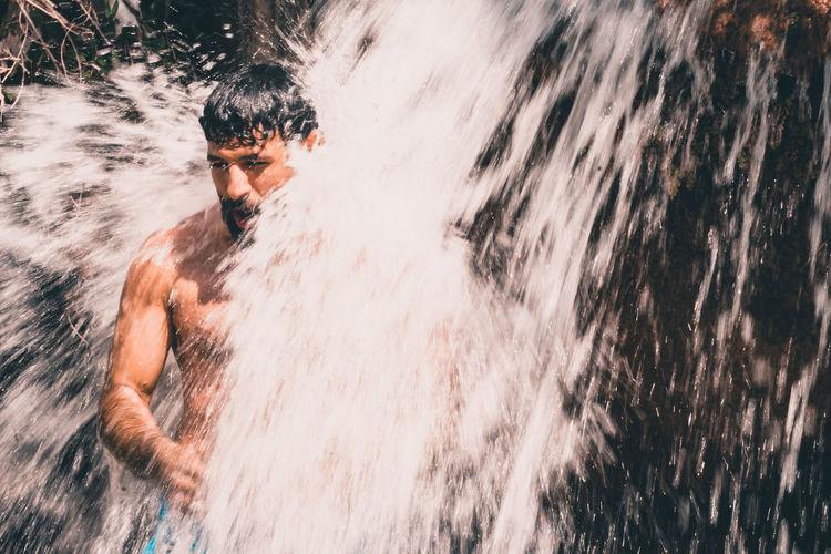 Shirtless man in waterfall