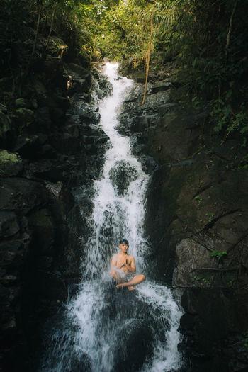 Man sitting on rock amidst waterfall