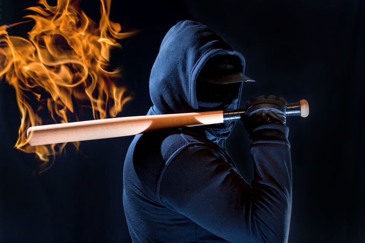 Digital Composite Image Of Fire By Man Holding Bat Against Black Background