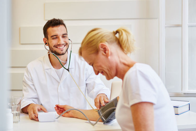 Smiling doctor examining patient in hospital