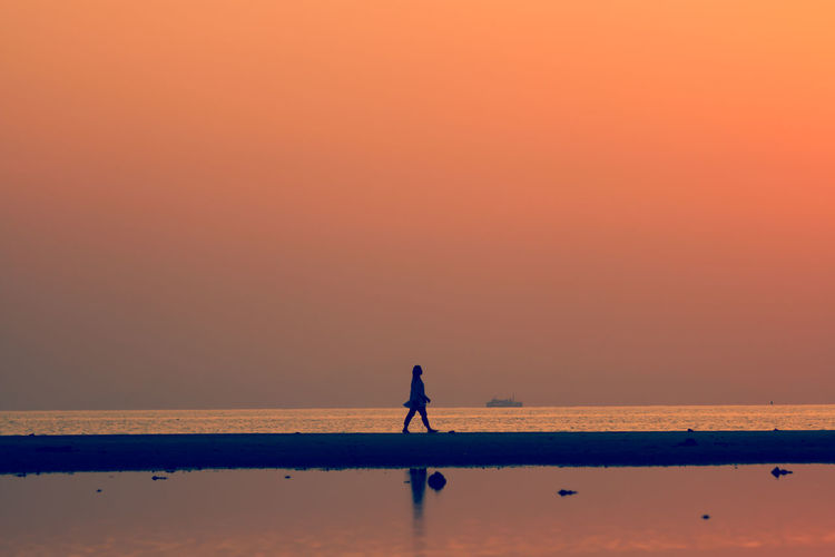 Silhouette man walking on beach against orange sky
