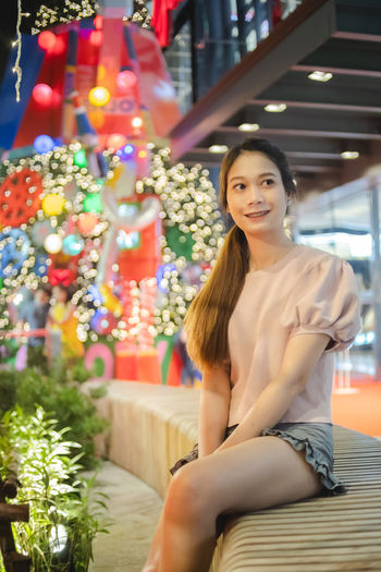 Portrait of smiling young woman sitting on illuminated christmas tree