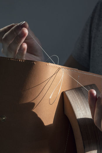 Midsection of man stitching cardboard