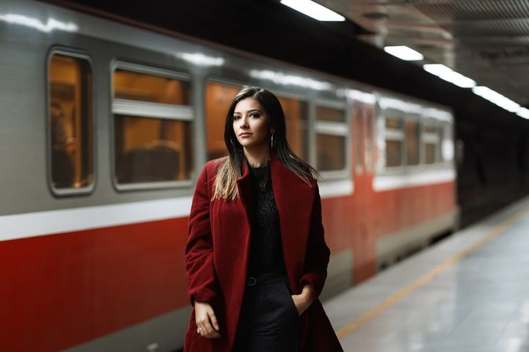 Portrait of beautiful woman standing at railway station