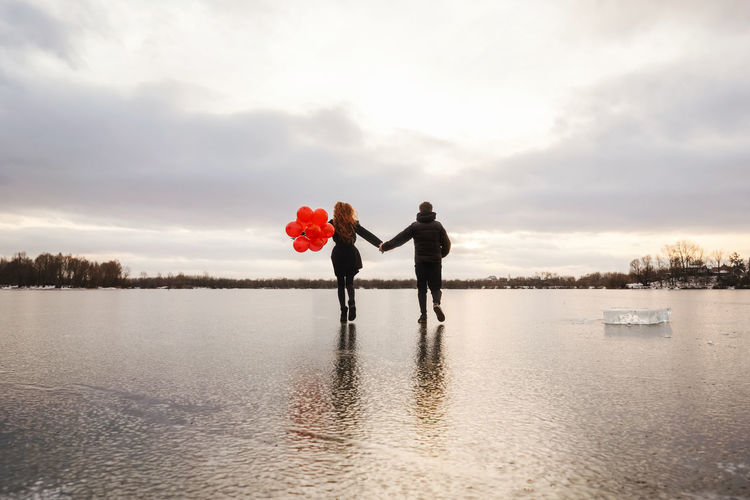 Rear view of couple holding hand walking on frozen lake against sky