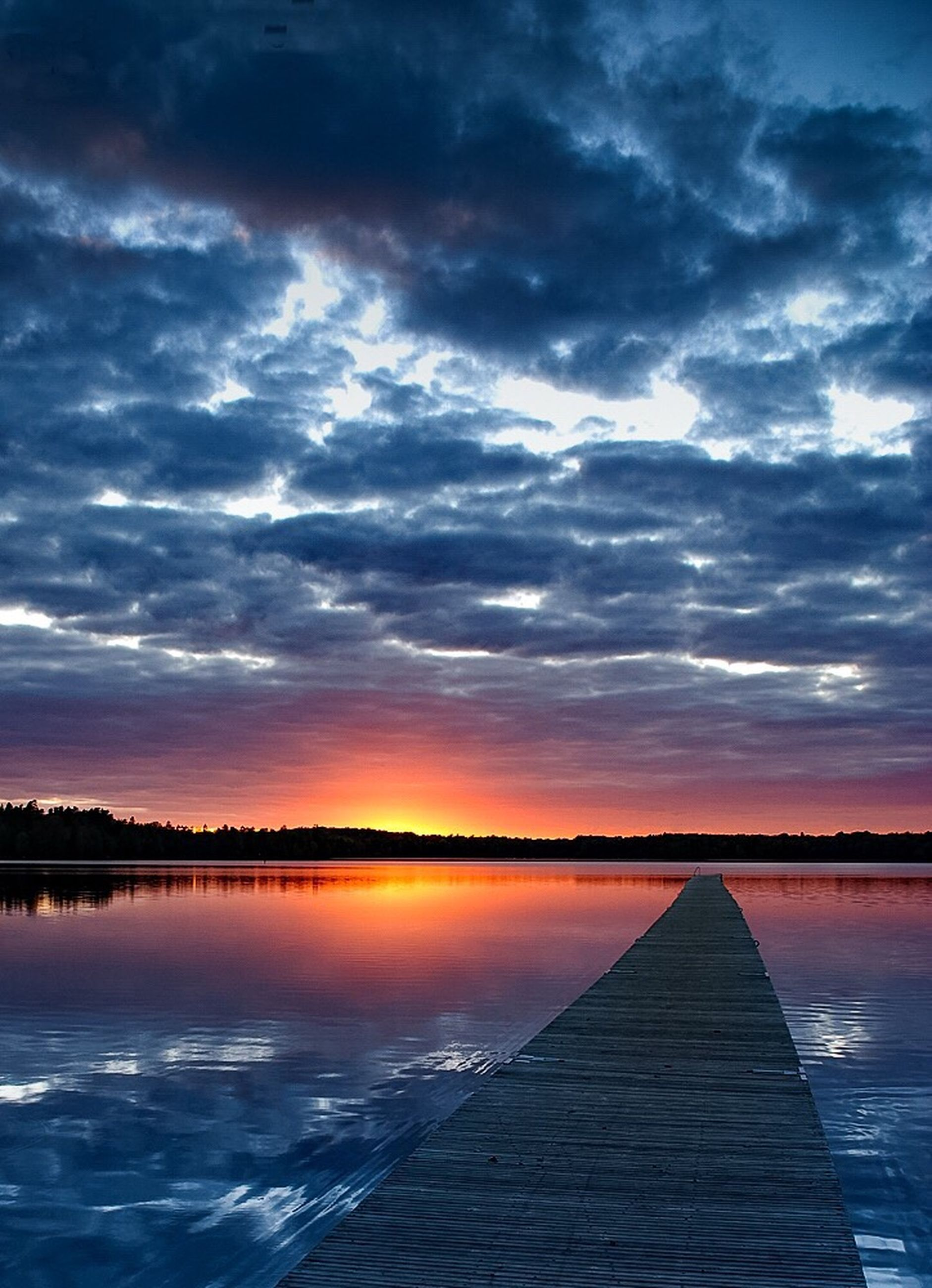 sunset, sky, water, cloud - sky, scenics, tranquility, tranquil scene, reflection, beauty in nature, lake, cloudy, orange color, cloud, nature, idyllic, dramatic sky, pier, waterfront, outdoors, weather