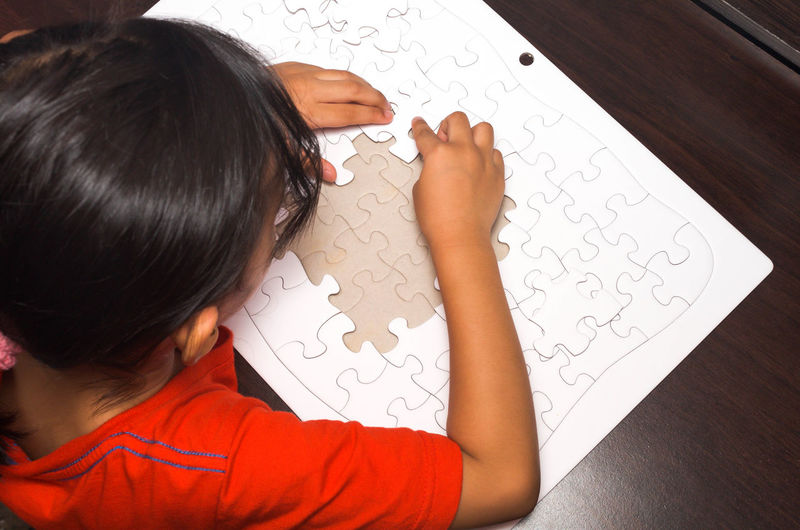 A little girl put the pieces of jigsaw puzzle to complete the mission. Business Challenger Desk Missing Mission Solving Concept Creative Hand Idea Indoors  Jigsaw Piece Jigsaw Puzzle Leisure Activity Little Girl Object One Person Pattern People Problem Put Puzzle  Puzzle  Strategy Together