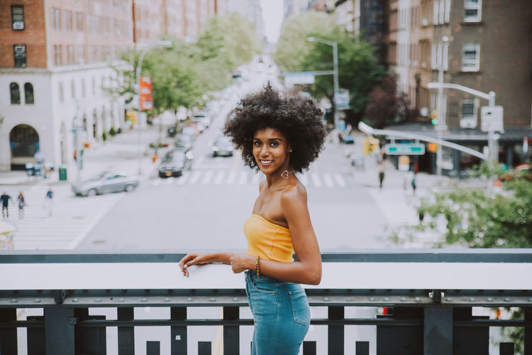 Side View Portrait Of Confident Young Woman With Afro Hairstyle Standing On Bridge Against City Street