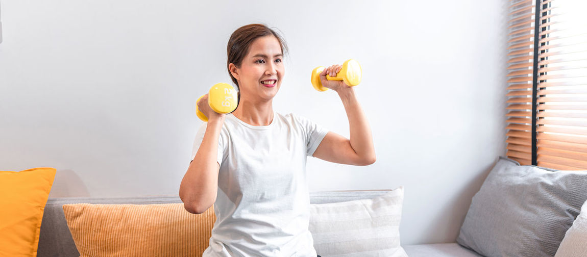 Young woman smiling while standing on sofa at home